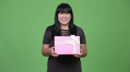 overweight : Beautiful overweight Asian woman smiling while holding gift box Stock Footage