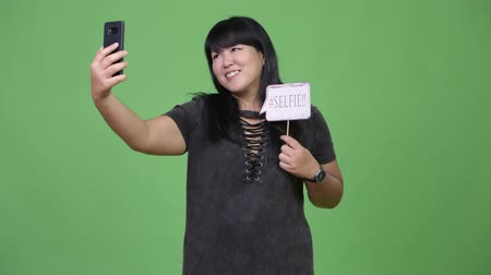 attitude : Beautiful overweight Asian woman taking selfie with paper sign Stock Footage