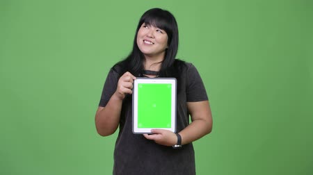 korhadt : Happy overweight Asian woman thinking while showing digital tablet