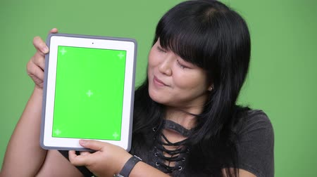 pankáč : Happy overweight Asian woman showing digital tablet