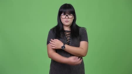 pankáč : Happy overweight Asian woman wearing eyeglasses with arms crossed