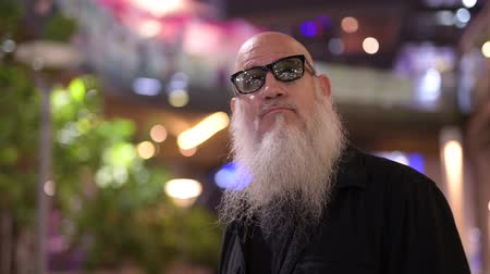 ponderando : Mature bald bearded tourist man waiting against view of the city at night