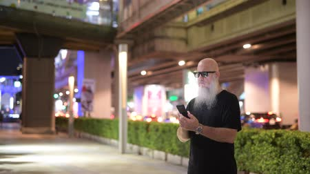 thought : Mature bald bearded tourist man using phone in the city at night