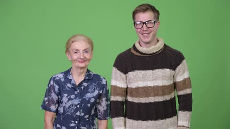 finnish : Happy grandmother and grandson smiling together against green background