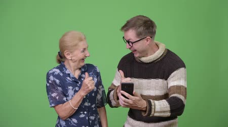 finnish : Happy grandmother and grandson using phone then giving thumbs up together Stock Footage