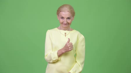 human like : Happy senior businesswoman smiling while giving thumbs up