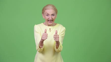 schválení : Happy senior businesswoman giving two thumbs up