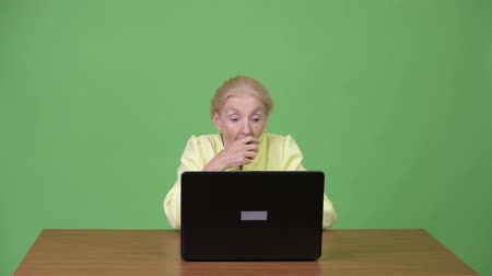 překvapení : Senior businesswoman using laptop and looking shocked