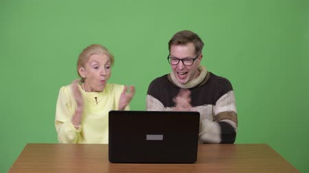 raising fist : Senior businesswoman and young handsome man using laptop and getting good news together