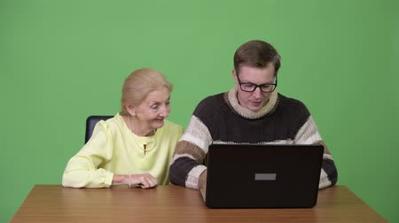 finnish : Happy senior businesswoman and young handsome man using laptop together Stock Footage
