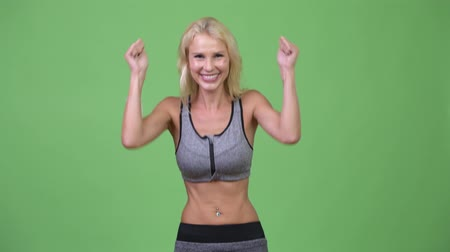 raising fist : Young happy beautiful woman looking excited ready for gym Stock Footage