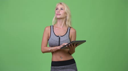 ponderando : Young happy beautiful woman thinking while using digital tablet ready for gym Stock Footage