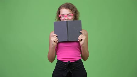 kolsuz : Young shy nerd woman with curly blond hair hiding behind book Stok Video