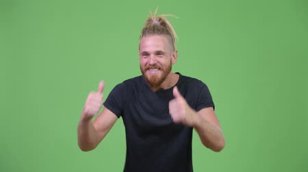 schválení : Happy handsome bearded man with dreadlocks giving thumbs up Dostupné videozáznamy