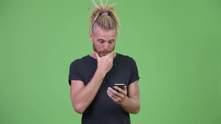 hippi : Handsome bearded man with dreadlocks using phone and getting bad news