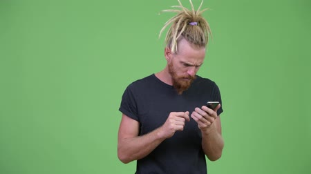 curioso : Handsome bearded man with dreadlocks using phone and looking shocked