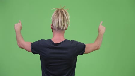 looking distance : Back view of bearded man with dreadlocks pointing finger Stock Footage