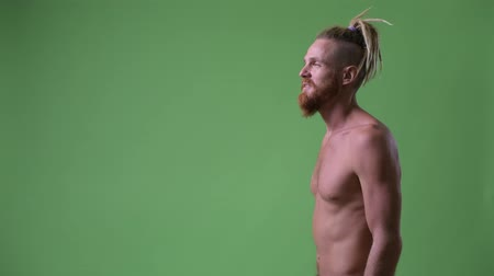 hippi : Profile view of handsome muscular bearded man with dreadlocks smiling shirtless Stok Video