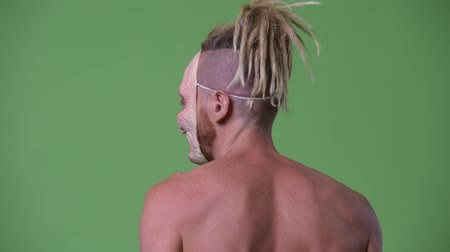 в середине : Shirtless man wearing scary mask while looking back Стоковые видеозаписи