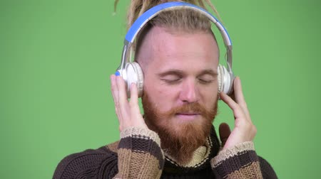 прослушивание : Handsome bearded man with dreadlocks wearing warm clothing while listening to music Стоковые видеозаписи