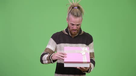hippi : Handsome bearded man smiling while opening gift box