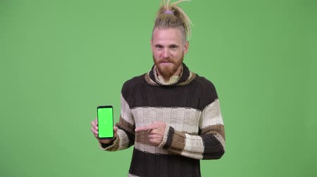dreadlock : Happy handsome bearded man showing phone and giving thumbs up