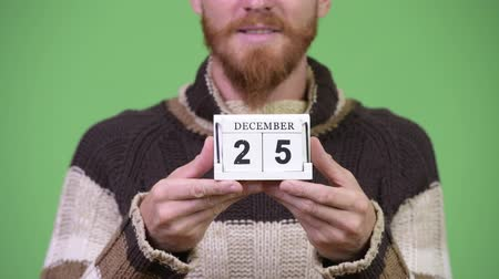 hippi : Happy bearded man smiling while holding calendar block ready for Christmas Stok Video