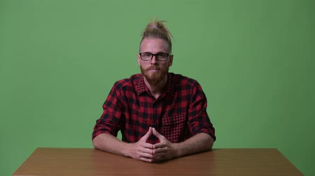 rastafarian : Handsome bearded hipster man being interviewed against wooden table