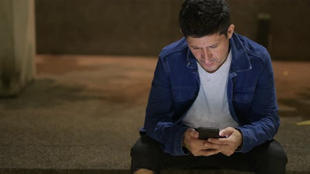 spanish street : Hispanic man using phone while sitting on the street in the city at night