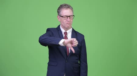 sem problemas : Studio shot of angry mature businessman giving thumbs down