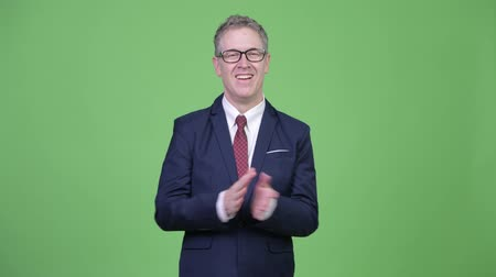 ovation : Studio shot of happy mature businessman clapping hands