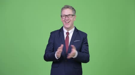 соглашение : Studio shot of happy mature businessman clapping hands