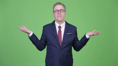doubt : Studio shot of mature businessman shrugging shoulders