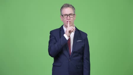 señal de silencio : Studio shot of mature businessman with finger on lips