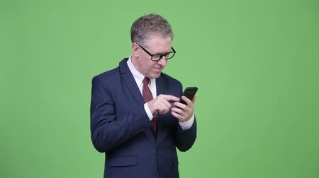 szare tło : Studio shot of mature businessman using phone and looking shocked