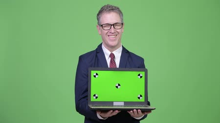 szare tło : Studio shot happy of mature businessman showing laptop