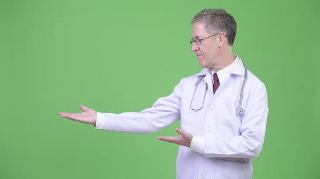 chroma key : Portrait of mature man doctor showing something