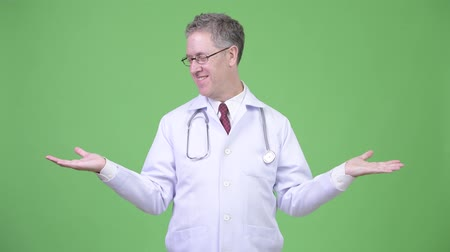 comparar : Portrait of happy mature man doctor comparing something