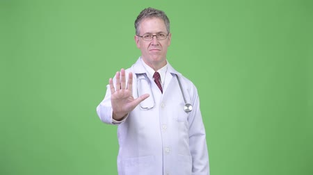 szare tło : Portrait of serious mature man doctor with stop hand gesture Wideo