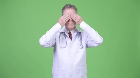 bilge : Portrait of mature man doctor covering eyes as three wise monkeys concept