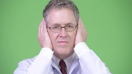 sayings : Portrait of mature man doctor covering ears as three wise monkeys concept Stock Footage
