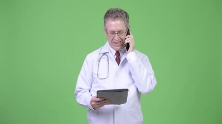 sebész : Portrait of mature man doctor talking on the phone while using digital tablet Stock mozgókép