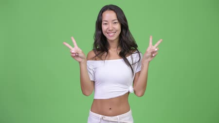 piekne : Young happy beautiful multi-ethnic woman showing peace sign Wideo
