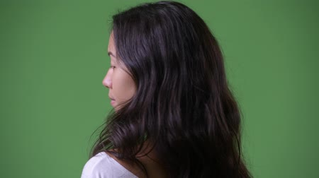 over the shoulder view : Young beautiful multi-ethnic woman looking back