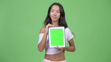 multikulturní : Young happy beautiful multi-ethnic woman thinking while showing digital tablet
