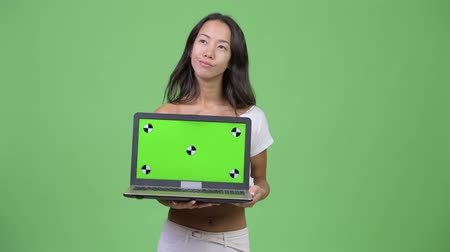дисплей : Young happy beautiful multi-ethnic woman thinking while showing laptop