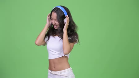 escuta : Young happy beautiful multi-ethnic woman listening to music