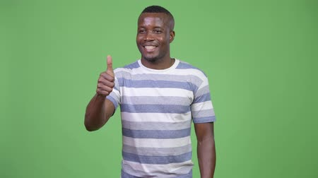 полосатый : Young happy African man giving thumbs up Стоковые видеозаписи
