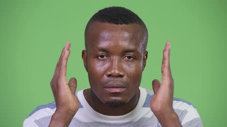 bölcs : Young African man covering ears as three wise monkeys concept Stock mozgókép