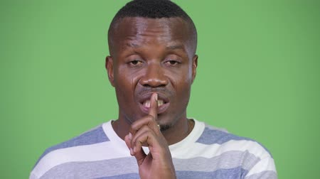 полосатый : Young African man with finger on lips